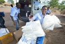 Workers unload insecticide-treated bed nets as they set up an outreach clinic in the Rhino Refugee Camp in northern Uganda, serving refugees from South Sudan. Photo by Paul Jeffrey.